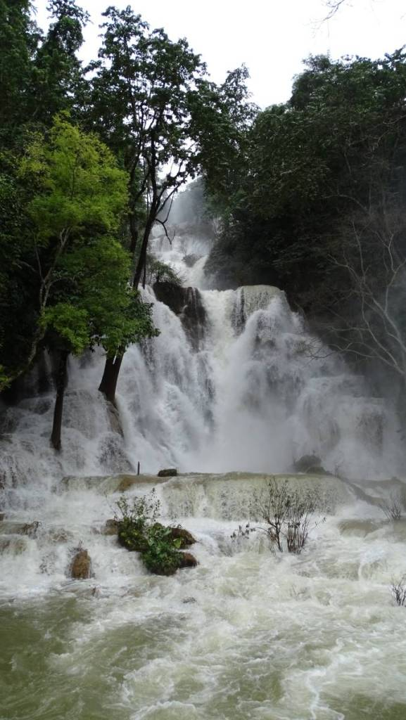 Huge, powerfull and high Muang Si waterfall with snow-white water going down in a few tiers, overflowing the trees growing at its sides.