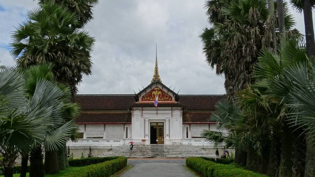 A monumental, white washed building of the National Museum in Luang Prabangand a row of palms leading to it