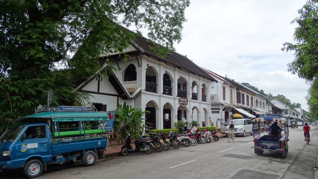 A small, blue shared truck similar to Thai songthaew stands on a main street in Luang Prabang old town, parked just  before a whitewashed colonial building turned into a hotel