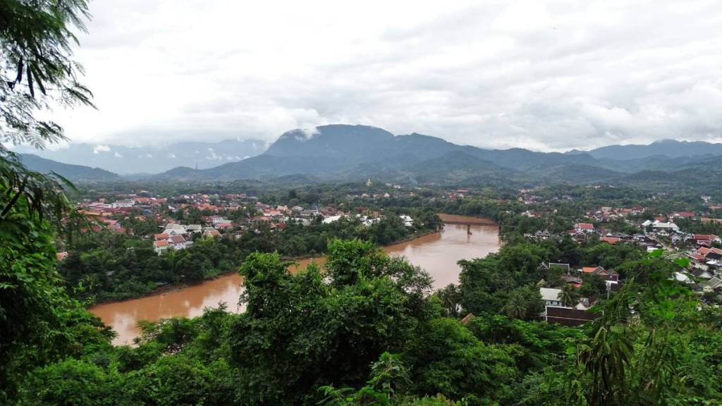 A view from Phousi hill at the brown coloured Mekong, trees on the hill, red roofs of Luang Prabang and mountains in the background