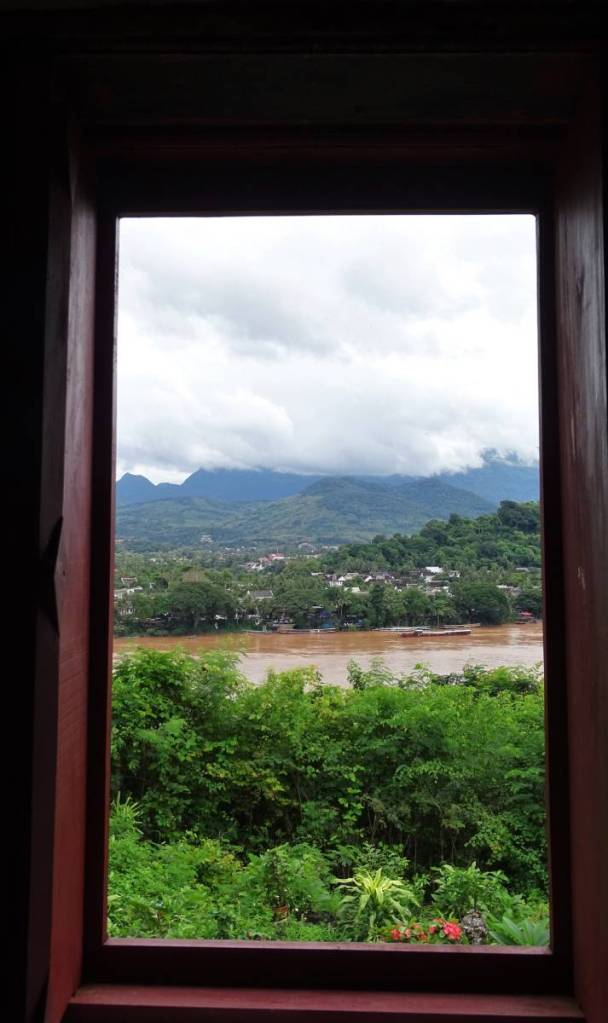 A wooden window frame and a view from a hilltop at a forest below, wide, muddy Mekong, roofs of Luang Prabang and forested mountains, half-hidden in the clouds