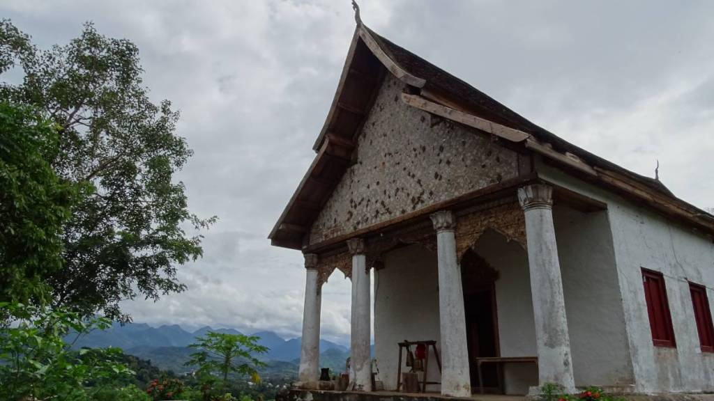 A dilapidated, whitewashed and relatively simple Wat Chom Phet with four columns on the front stands on the top of a hill, with a mountain range in the background