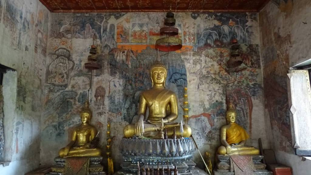 An interior wall of a wat covered with faded murals and 3 seated Buddha statues at Wat Pa Huak in Luang Prabang