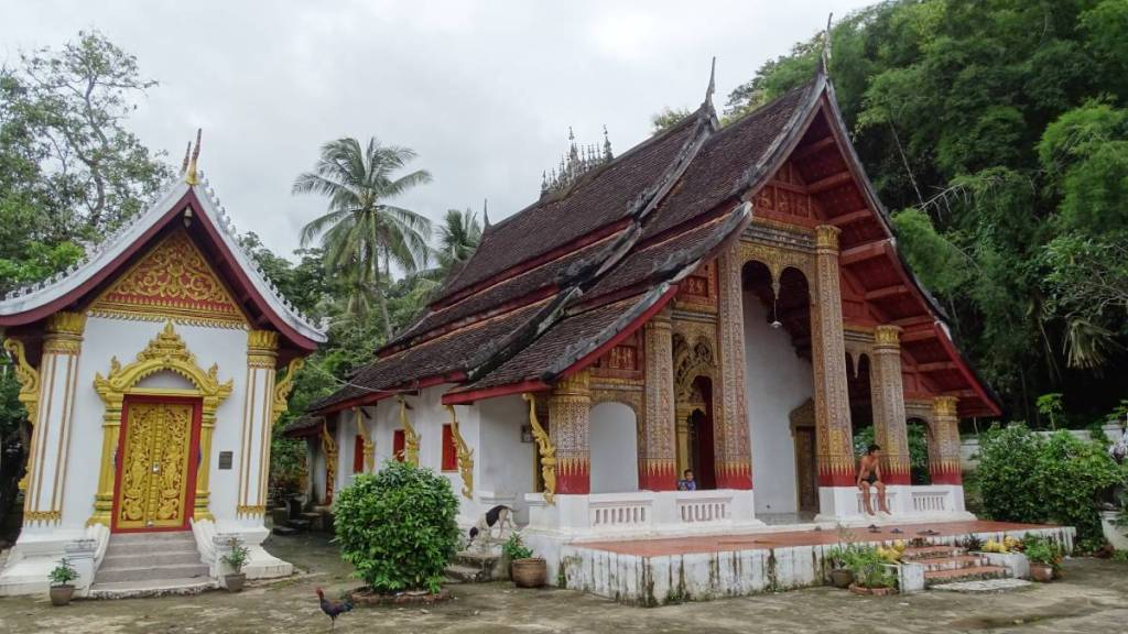 Wat Xieng Men stands right next to a wall of forrest. It has two-tiered roof and a porch, where a bare-chested boy sits.