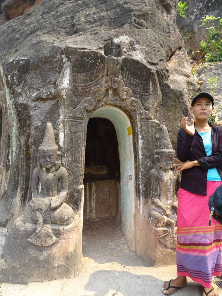 A Burmese female guide wearing a baseball cap and a pink sarong standing in front of one of the ancient cave temples in Monywa