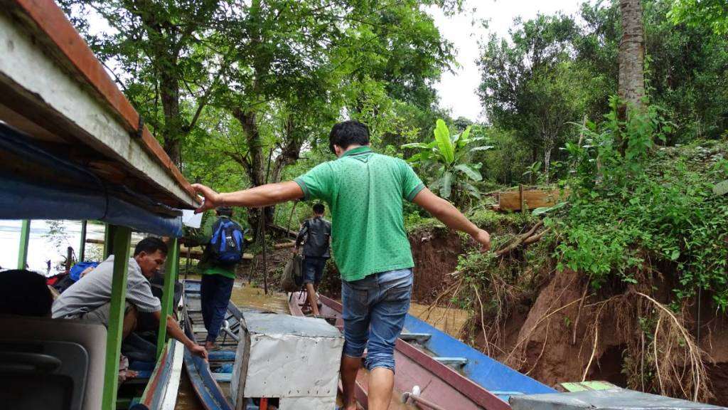 Laotian peopel walk down three narrow boats mooring at the cut banks.