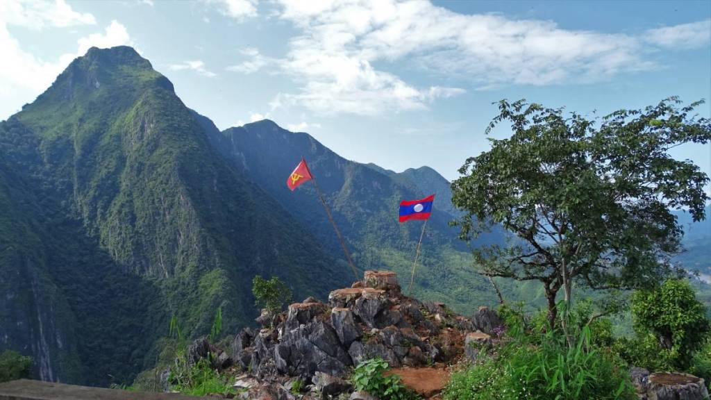 A Laotian and hammer and sickle flag stuck into the pile of rocks on the Pha Daeng peak, sharp green rocks behind it