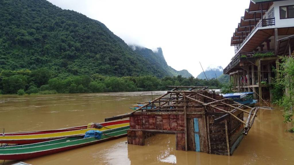 A ruined shack and a guesthouse in Muang Ngoi half-submerged by the river and a few colourful wooden, narrow boats moored nearby