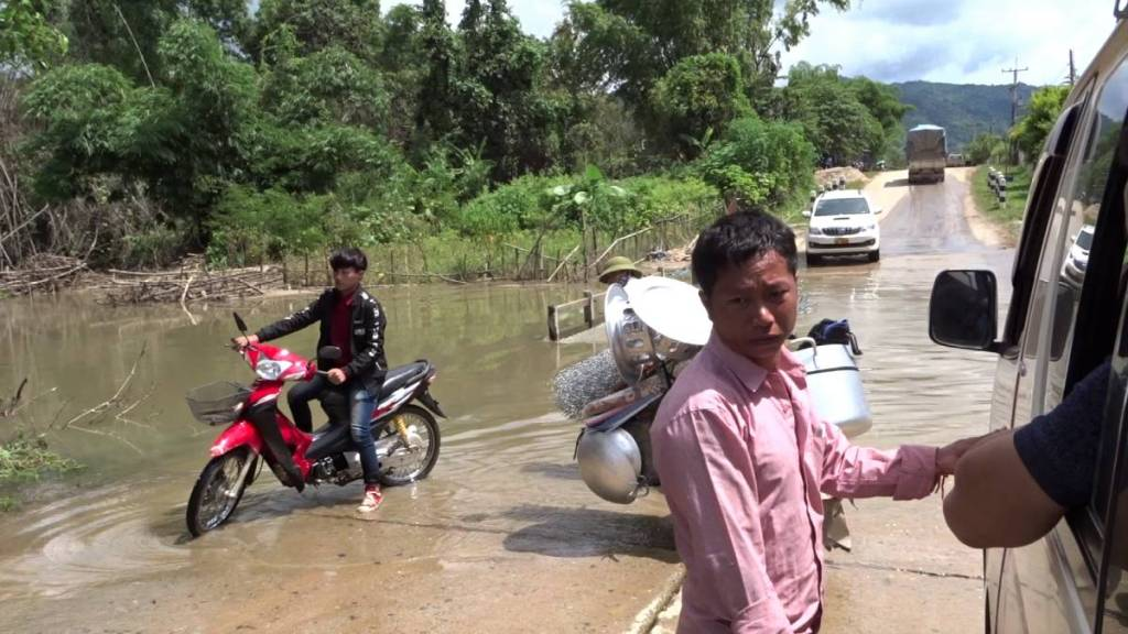 The minivan driver standing in the water on the flooded stretch of the road outside Phonsavan, while a motorbike and a bike filled with cookware are crossing the water