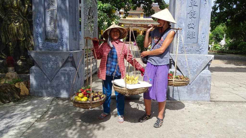 A Vietnamese street fruit seller in Hoi An is posing to a photo with the author, both wearing conical hats and carrying baskets on the pole