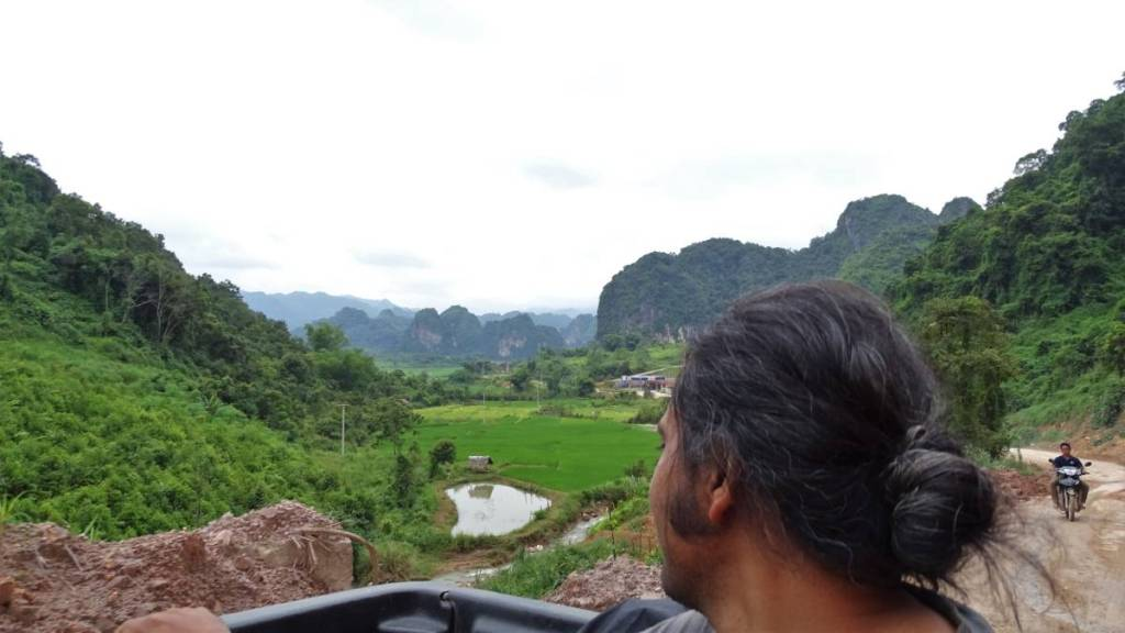 Sayak looking out of a pick-up truck onto a dirt road,  green paddy fields and karst landscape behind him.