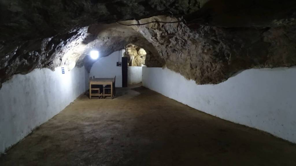 An elongated chamber inside one of Vieng Xai cave with white- washed walls, natural rock ceiling and a table with chairs in one corner