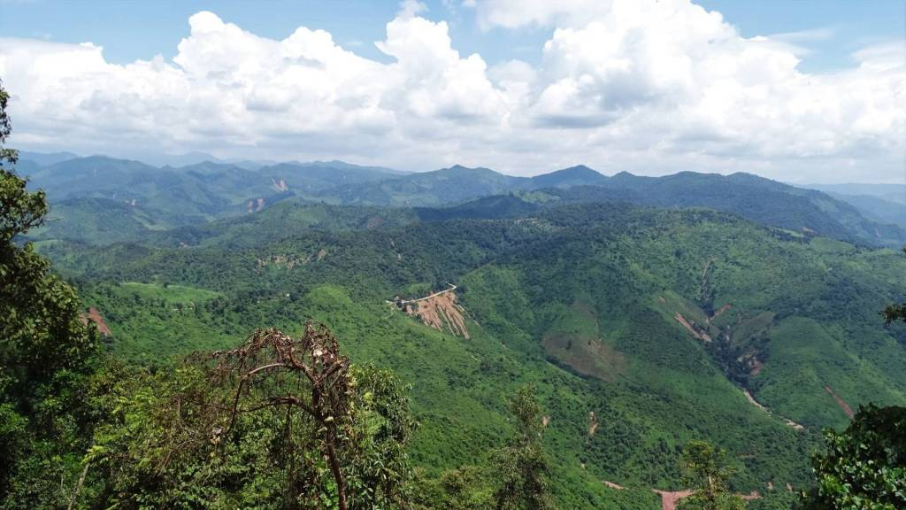 Panoramic views at the forest-covered mountains and a narrow strip of a road on a route from Phonsavan to Sam Neua