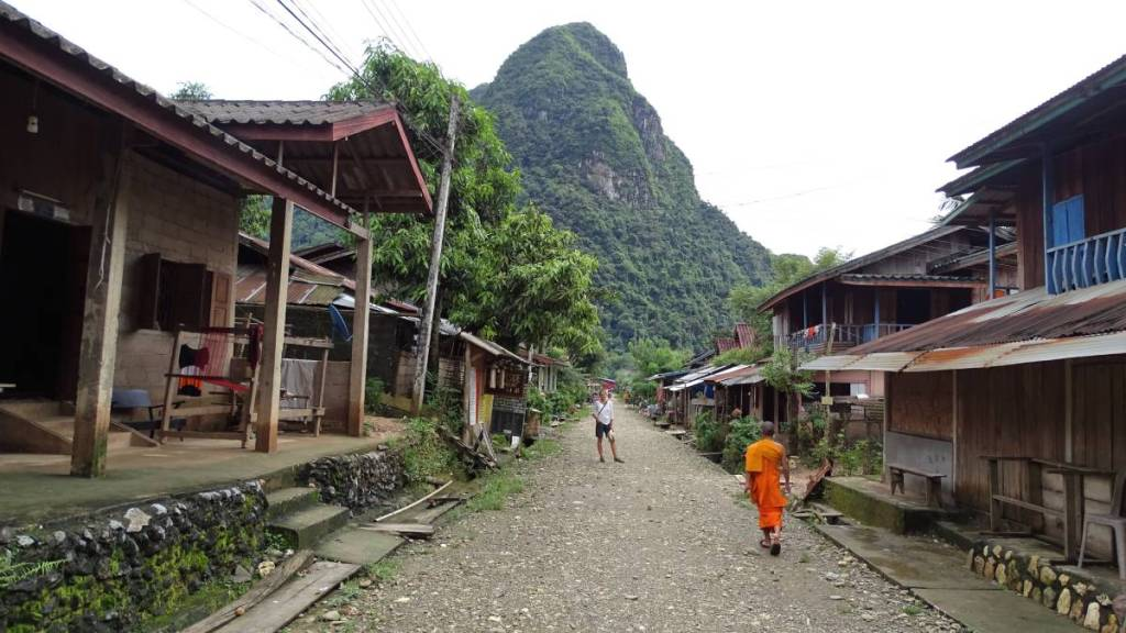A streetview in Muang Ngoi village: two rows of wooden houses,, pebbled street and karst rocks in the distance