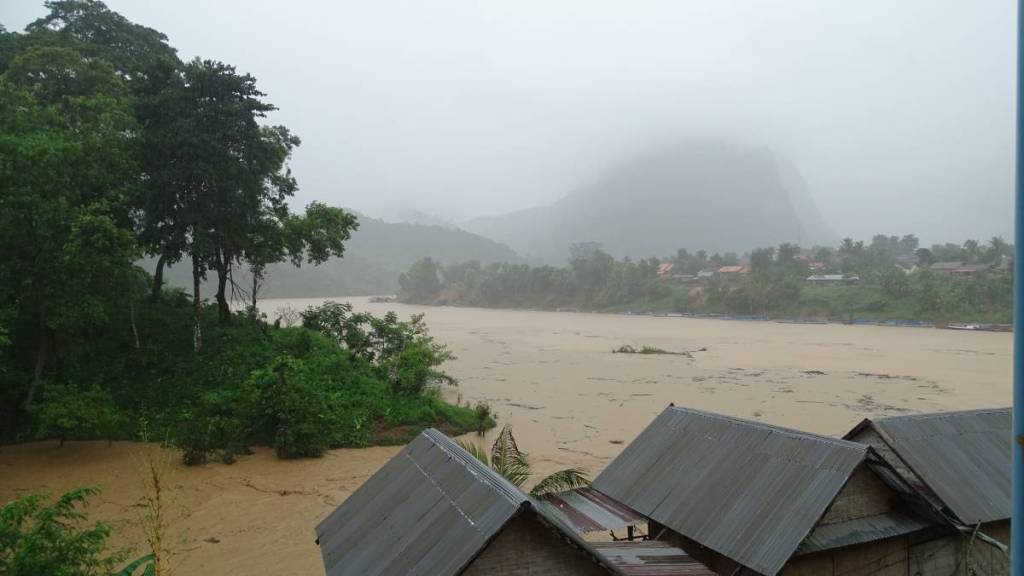Fast flowing, swollen and brown Nam Ou river and mist-covered mountains in the background