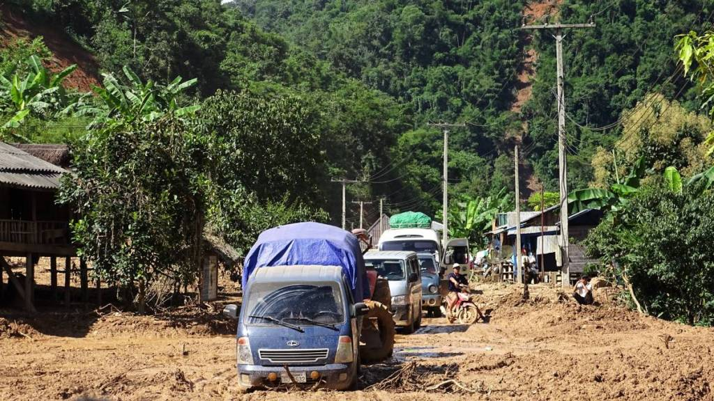 A string of minivans and trucks wade through a deep mud covering the road in the middle of a Laotian village