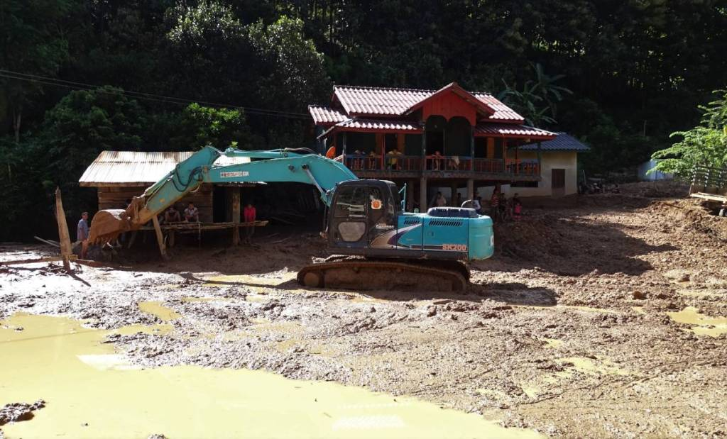 A digger clearing up the watery mud from the area in front of the stilted wooden houses in a Lao village. The villagers watch by from the shadow of their verandahs
