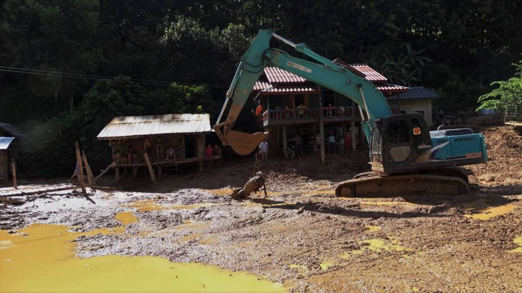 A digger pulling a scooter out of deep, watery mud in front of the villagers sitting in the shadow of their wooden huts