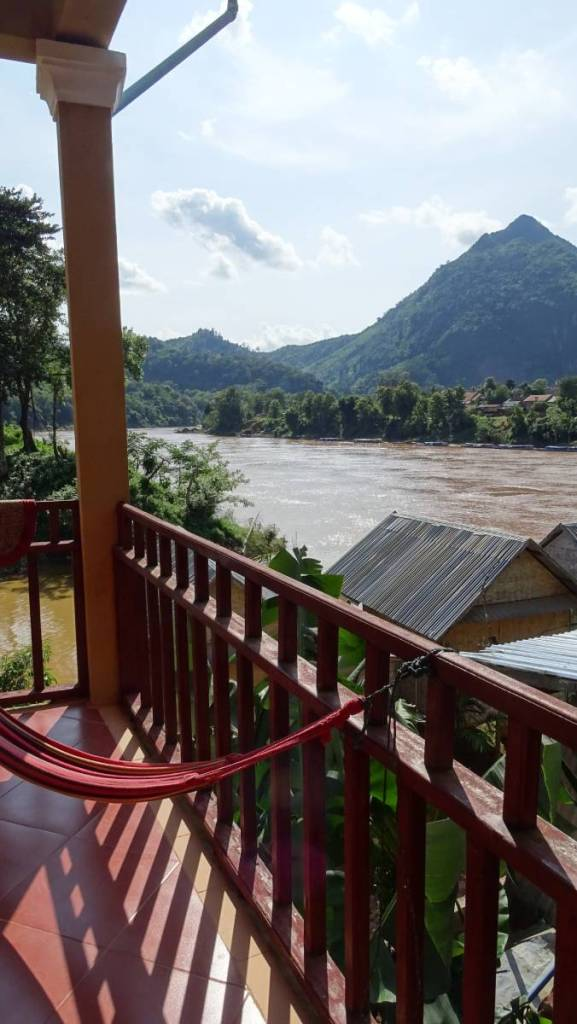 A balcony of a guesthouse with a view at the Nam Ou river and the forested mountains in the background