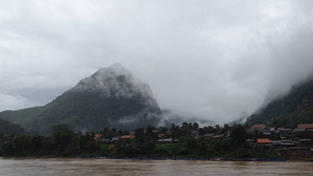 A view at the Nam Ou river, Nong Khiaw village on the other bank and mist shrouded karst rocks in the background