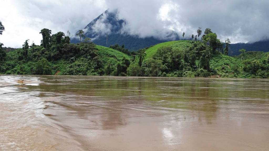 Brown waters of Nam Ou river, sunny, green hills and a forest clad mountain covered in the clouds
