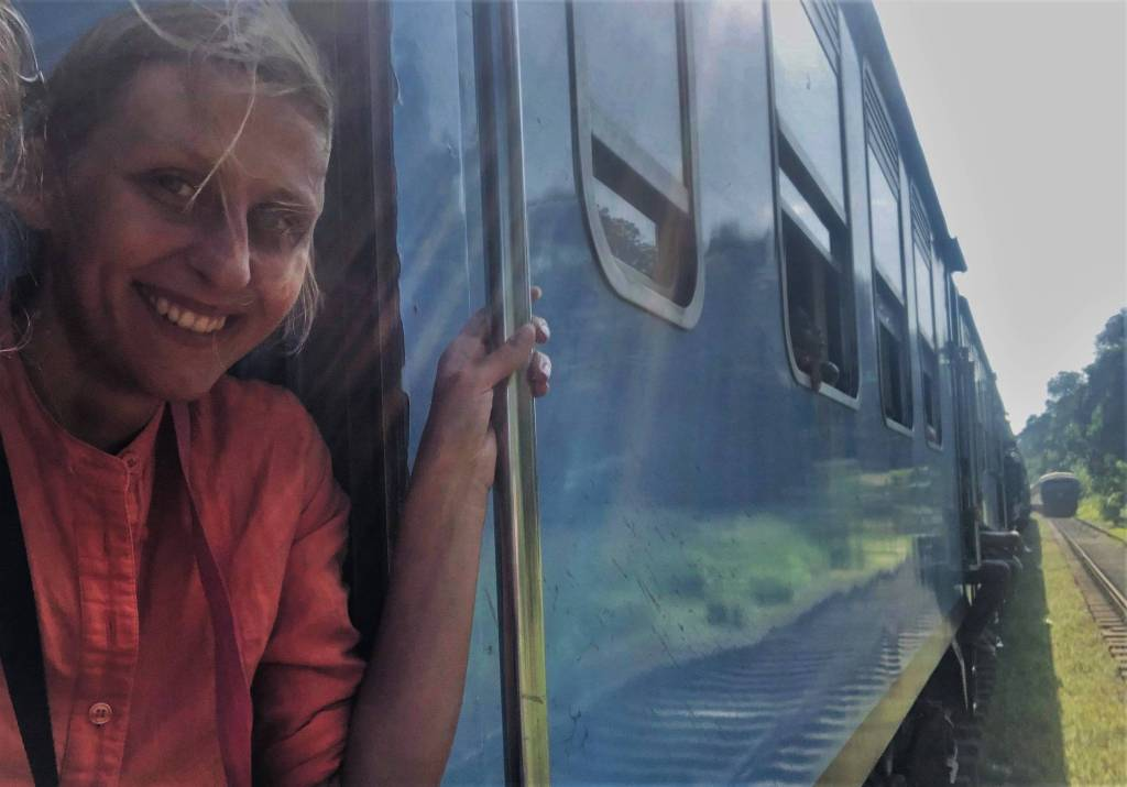 Author enjoying budget trip on the steps of the third class train in Sri Lanka