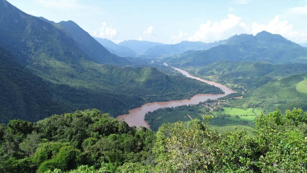 A panoramic view at the green, sharp mountains and Nam Ou river winding between them