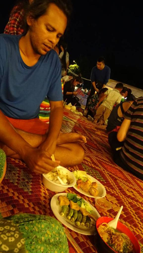 Sayak sitting cross-legged on a straw mat among Khmer people on a night market in Phnom Penh, a selection of BBQ skewers and noodle soups in front of him