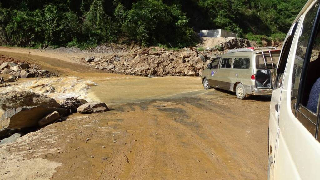A minivan covering a flooded section of the road between Phonsovan and Sam Neua