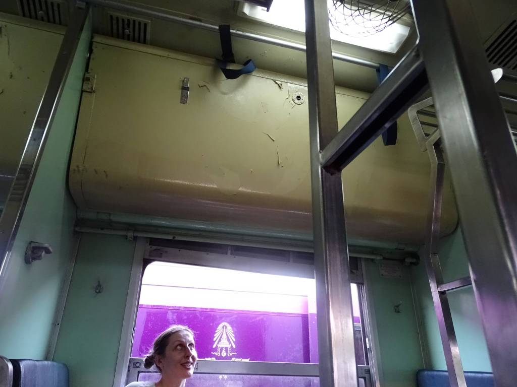 The author looking up at the folded berth in a second class sleeper train in Thailand
