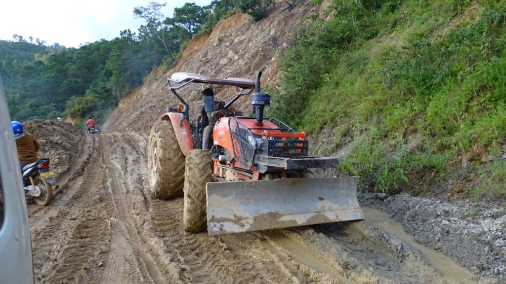 A red tractor cum bulldozer dealing on an extremely muddy section of the road in the Laotian mountains