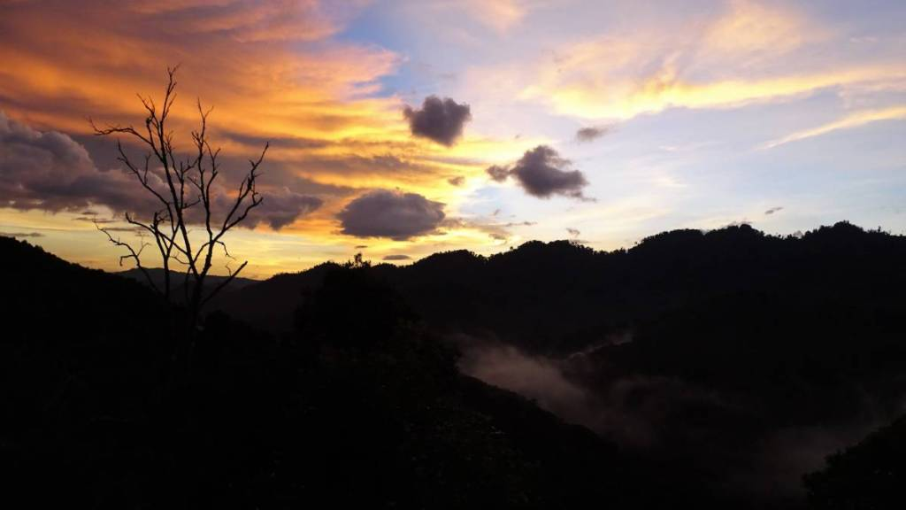 Orange clouds and the mountains already in the deep shadow, with the mist raising from the valley