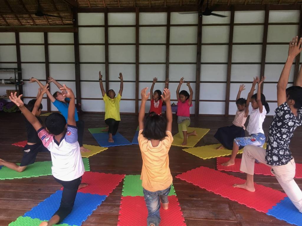 A group of school-aged Cambodian kids practicing yoga in a yoga studio in Siem Reap