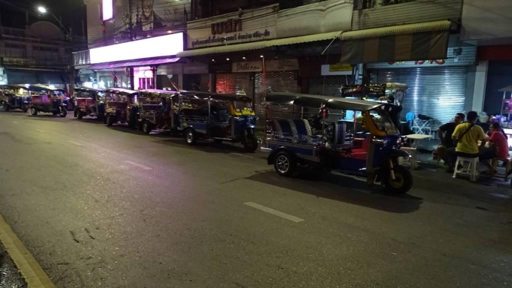 A row of empty tuk-tuks parked on a Bangkok street at night