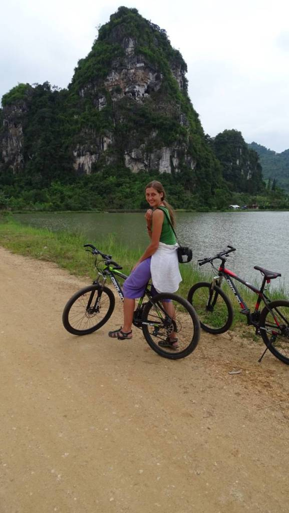 The author on a mountain bike  in front of a pond in Vieng Xai, with a tall karst rock behind her