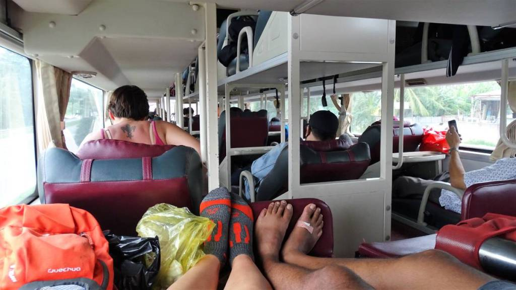 The interior of a Vietnamese sleeper bus with three rows of bunk reclining seats
