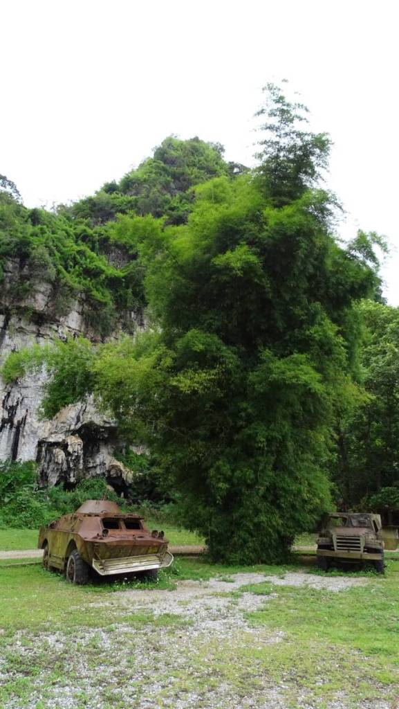 A rusty armoured vehicle and a military car standing in front of the caves hidden in the karst rocks in Vieng Xai in Laos.
