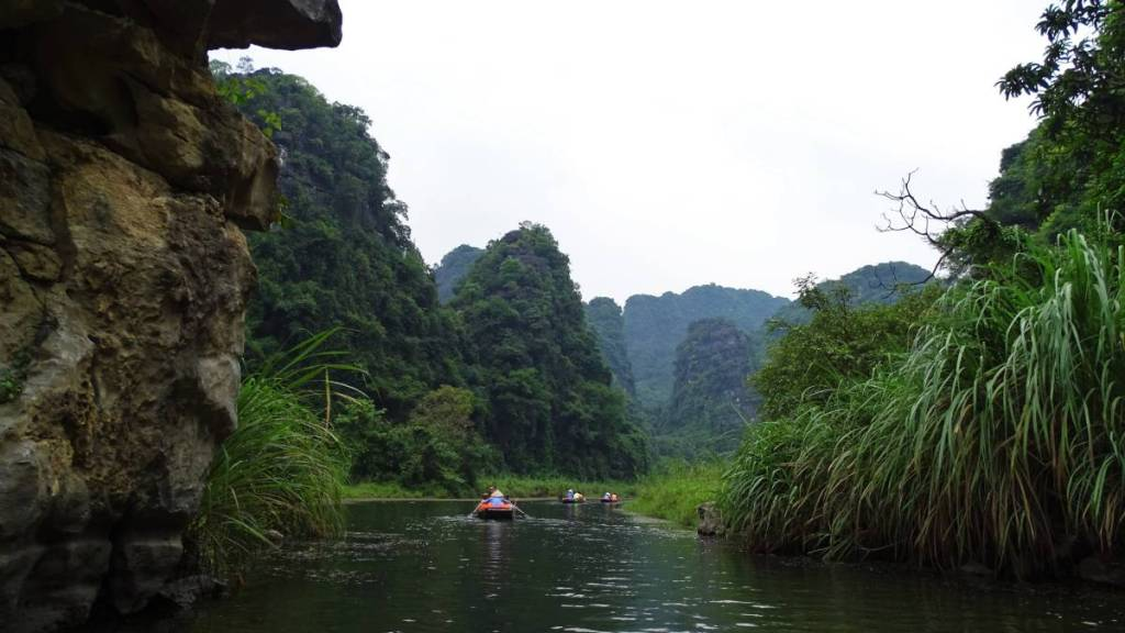 Tourists boats on the river flowing through karst landscape near Ninh Binh in Vietnam.