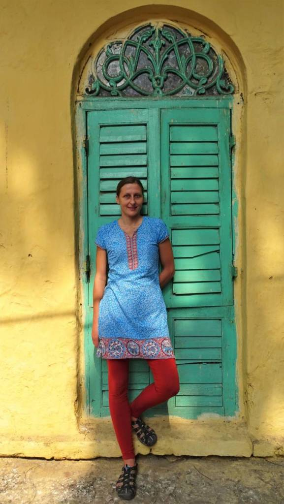 The author standing behind an old building in Kolkata, wearing a kurta (Indian tunic) and leggings