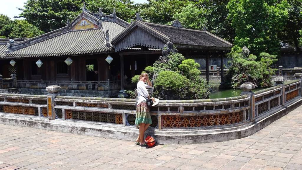The author posing in front of the concubine quarters in the Imperial City of Hue, wearing a light skirt and 3/4 top