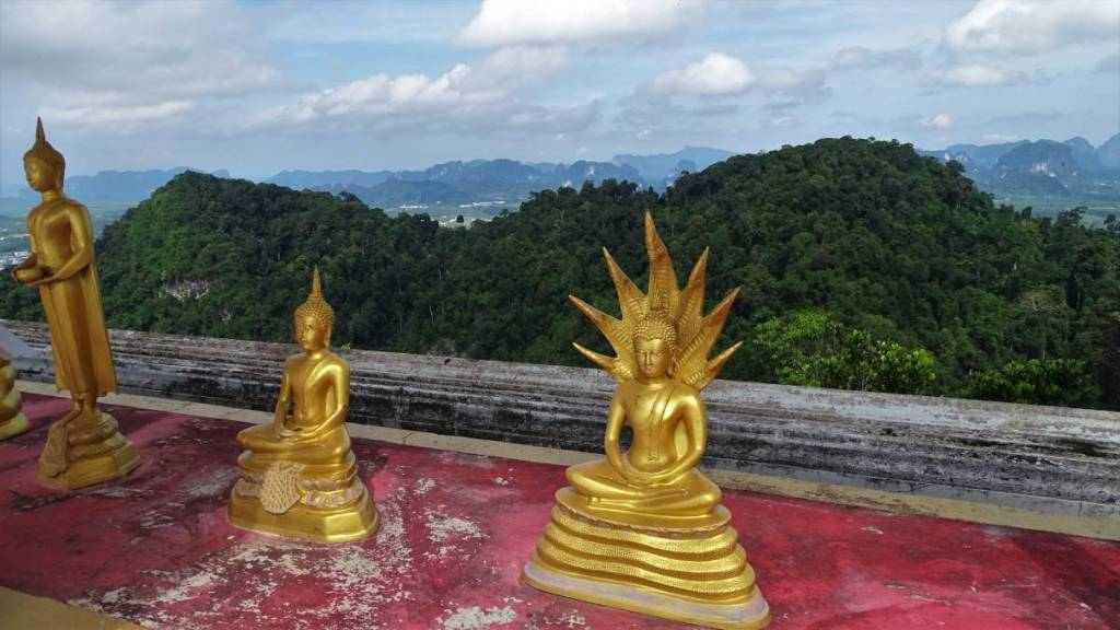 Golden figures of Buddha on the ledge of a terrace on top of the Tiger Hill in Thailand. Behind them, forested mountains and karst rocks.