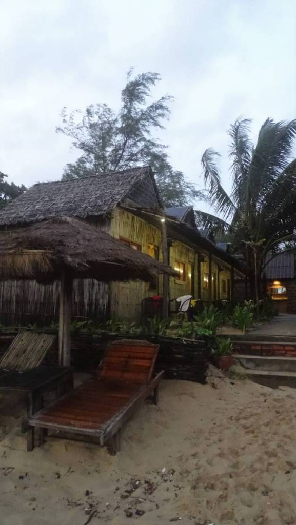 Wooden sunbeds on the beach and a row of bamboo huts in Otres