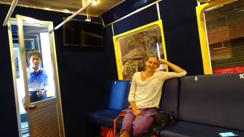 The author sitting on the empty bench inside the A/C train car from Phnom Penh to Sihanoukville