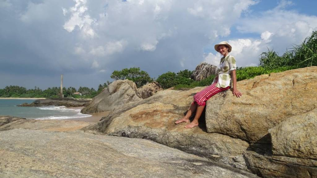 Author sitting on a rock on the Sri Lankan coastline, wrapped in a local cotton sarong, wearing a light shirt and a sun hat