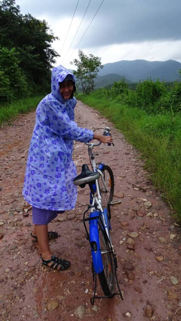 The author wearing a thick, flower-pattern poncho leads a bicycle through a dirt road in the mountainous region of Laos