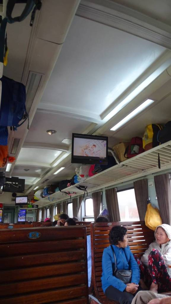 The interior of a hard seat train car in Vietnam: wooden benches and screens with videoclips