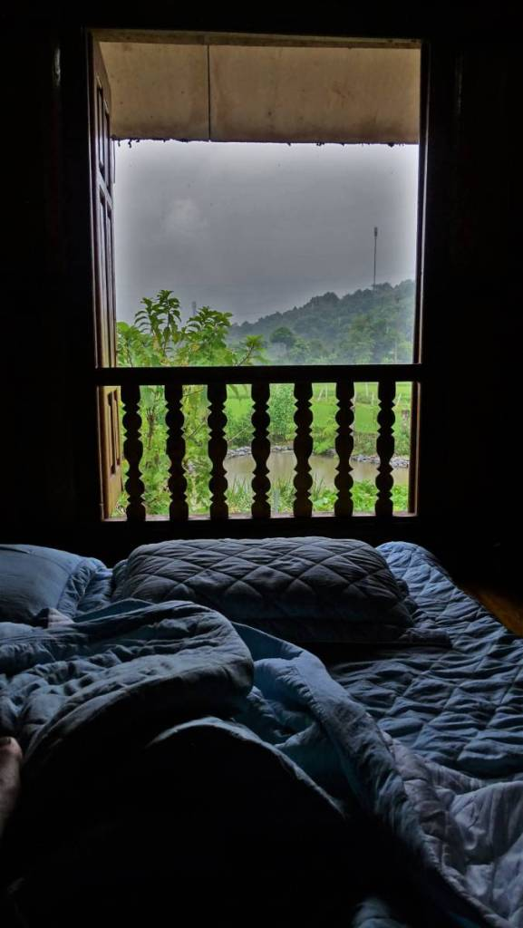 A mattress spread on the floor and the view at the paddy through the window in a homestay in Ha Giang