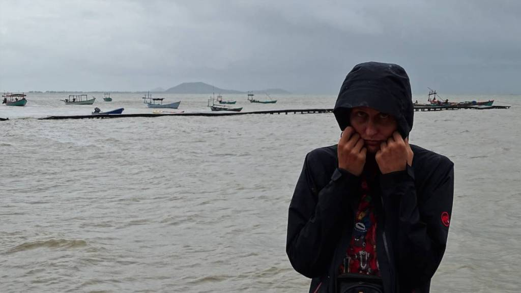The author makes a sad face when she covers her head with a hood of a waterproof jacket next to a half-submerged pier at the seaside in Kep
