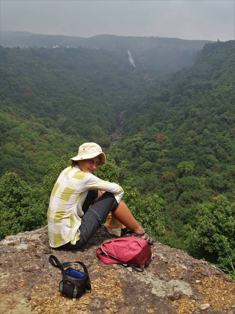 Author sitting on the edge of a cliff overlooking a valley and a waterfall, with her backpack and a camera back lying close to her