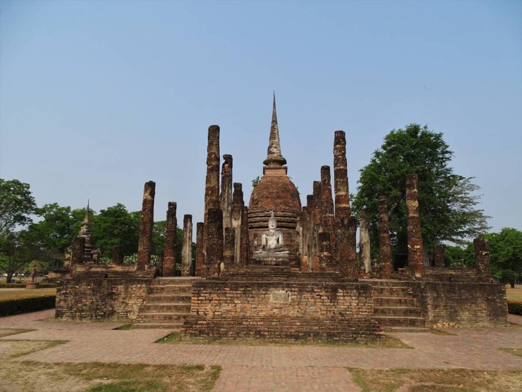 Ruins of a brick Buddhist temple in Sukhothai, Thailand. Only  the base, columns, a seated Buddha statue and a stupa survive.